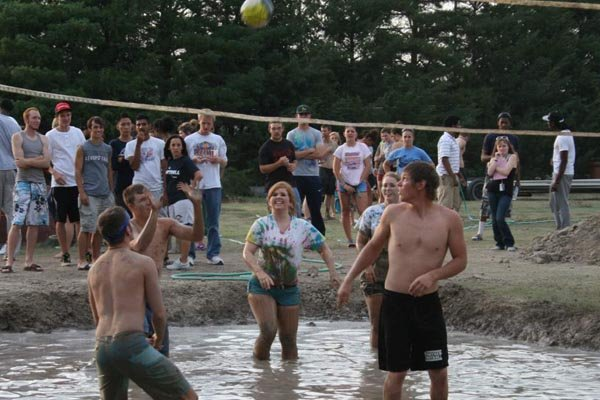 Students play mud volleyball during orientation week.