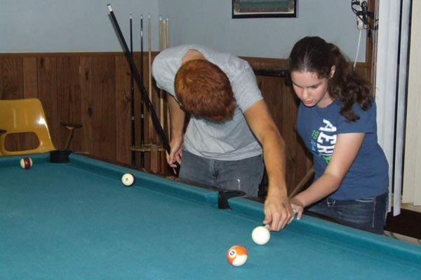 CCC student teaches fellow student to play pool.