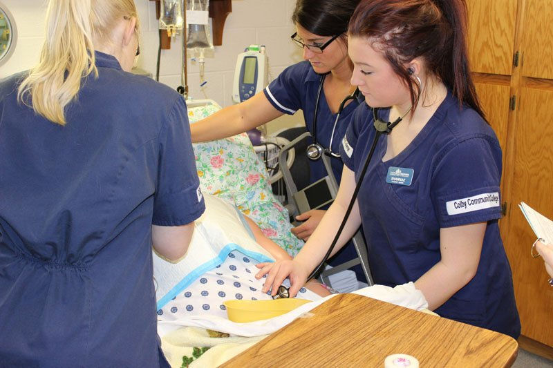 Students checking vital signs on a patient