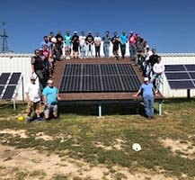 Boot camp students surrounding a solar panel on a mock roof top.