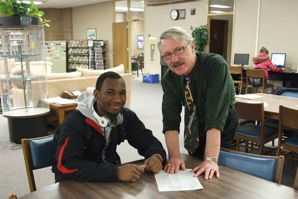 Business Instructor Bob Selby and student in library.